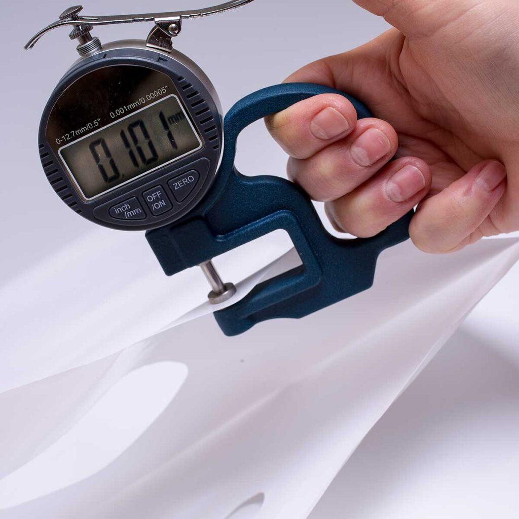 Микрометр измеряет плотность пакета Банан. На шкале прибора, цифра – 101mk.