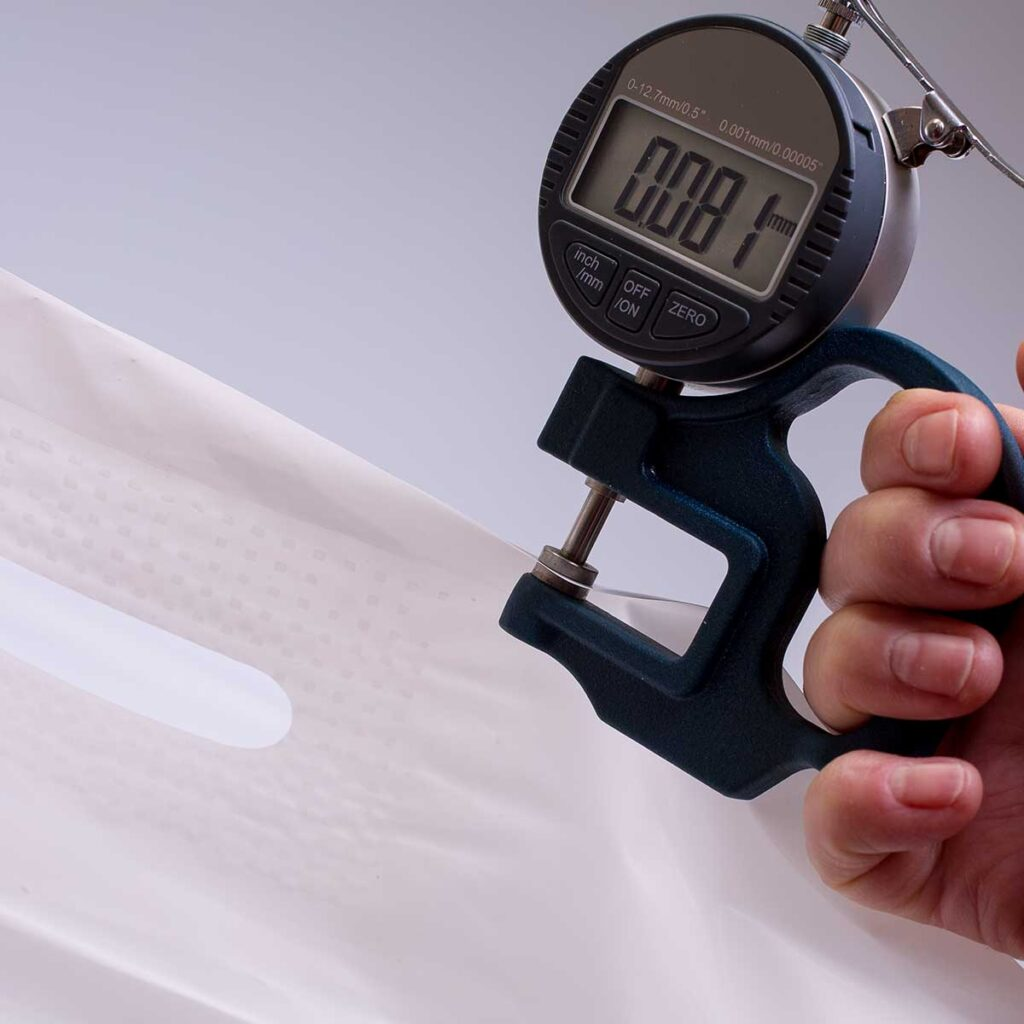 Микрометр измеряет плотность пакета Банан. На шкале прибора, цифра – 81mk.