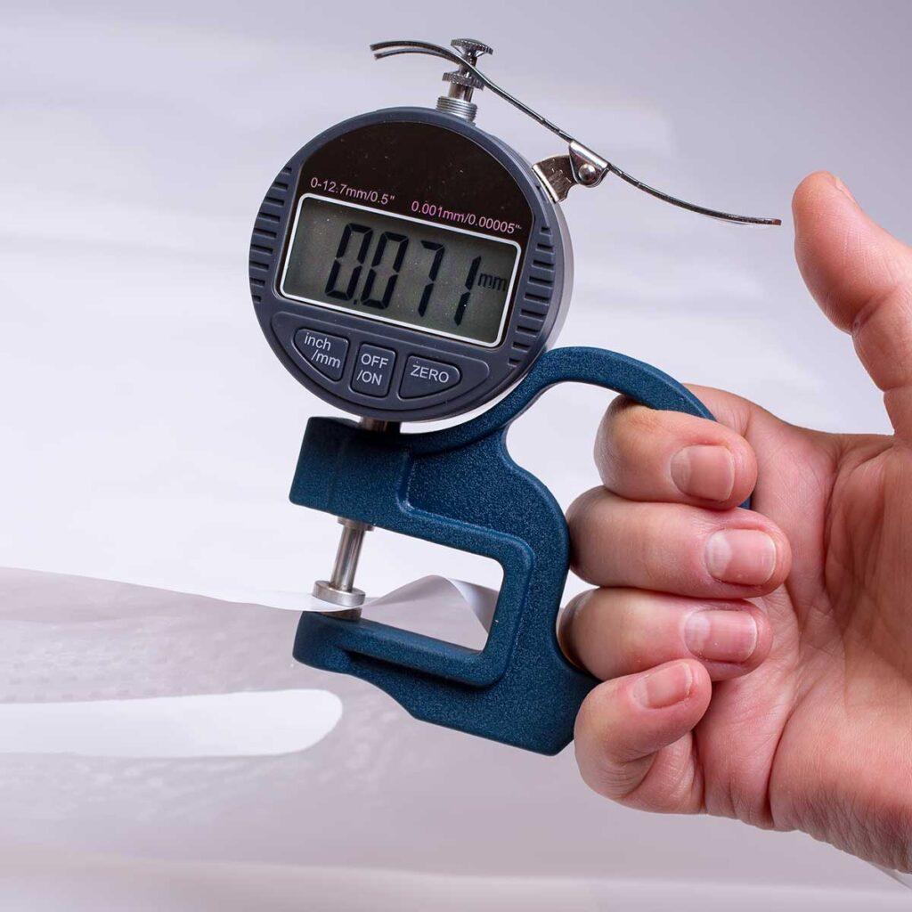 Микрометр измеряет плотность пакета Банан. На шкале прибора, цифра – 71mk.
