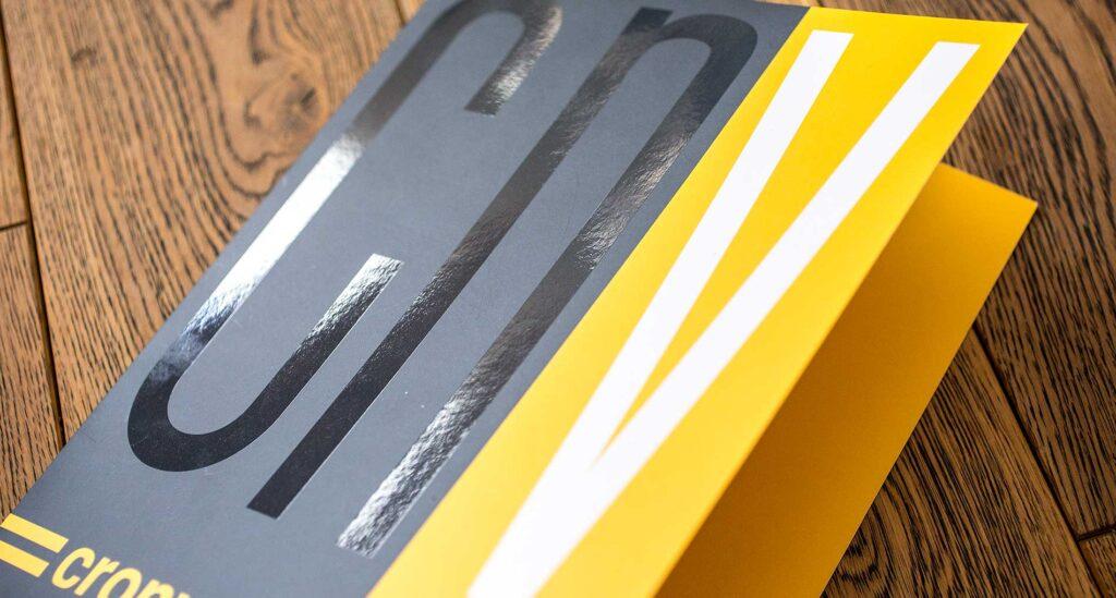 Фирменная папка с логотипом на деревянной доске.